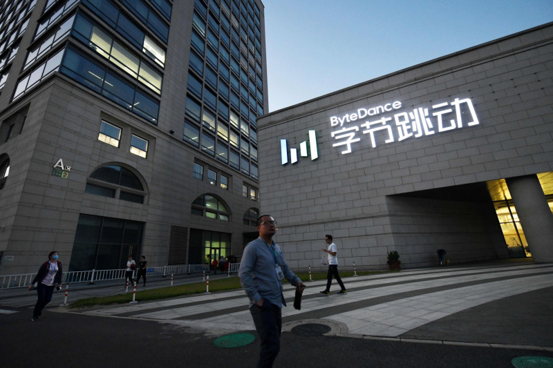 أشخاص يمرون بالقرب من مقر بايت دانس، الشركة الأم لتطبيق مشاركة الفيديو تيك توك، في بكين