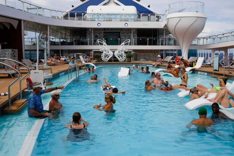 """المسافرون في حوض السباحة الخاص بالمنتجع على متن السفينة السياحية """"سيليبريتي إيدج"""" في يونيو، كجزء من أول رحلة مدرة للدخل أبحرت بعد الوباء"""