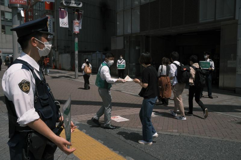 موظف من حكومة مدينة طوكيو يوزع منشورات تطلب من الناس البقاء في منازلهم، في 9 مايو 2021