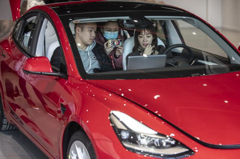"""عملاء يتفقدون سيارة """"تسلا"""" من طراز """"إس"""" في قاعة عرض في شنغهاي، الصين"""
