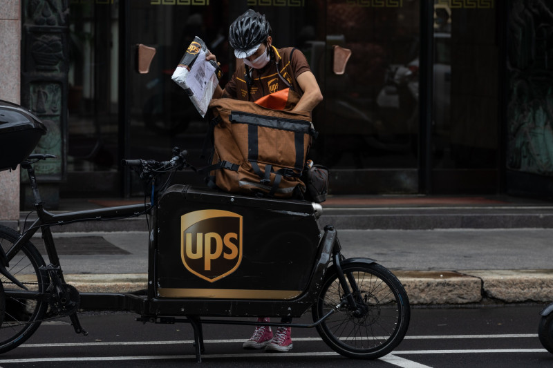 "سائق توصيل تابع لشركة ""يو بي إس"" يتعامل مع طرد بجوار دراجته في ميلانو، إيطاليا"