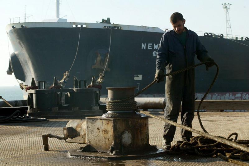 عامل يربط حبلاً من ناقلة نفط راسية في محطة نفط البصرة جنوب العراق