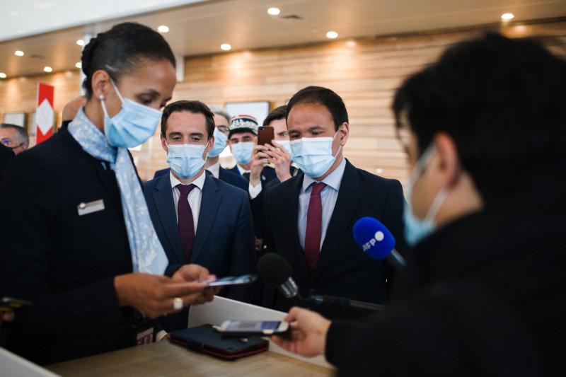 """جان بابتيست دجيباري، الثاني من اليسار، يشاهد طاقم الخطوط الجوية الفرنسية وكيه إل إم وهم يستعرضون تطبيق تعقب فيروس كورونا عبر الهاتف الذكي """"TousAntiCovid"""" في مطار أورلي في باريس، بتاريخ 27 أبريل."""