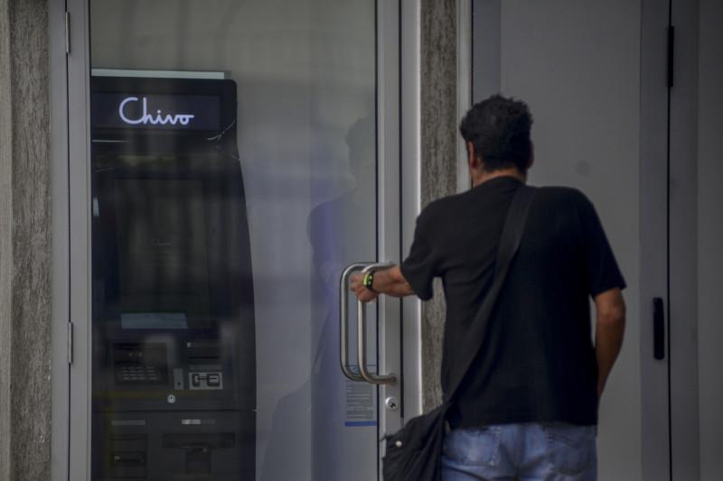"""أحد المارة يفتح باب كشك توجد به ماكينة صراف آلي تشيفو خاصة بعملة بتكوين في ميدان """"جيراردو باريوز بلازا"""" في """"سان سالفادور"""" بالسلفادور . بدأت السلفادور في تركيب ماكينات صرف آلي خاصة بـ""""بتكوين""""، تسمح لمواطنيها بتحويل العملة المشفرة إلى دولار أمريكي وسحب المبلغ نقداً في إطار خطة الحكومة لجعل العملة المشفرة عملة قانونية"""