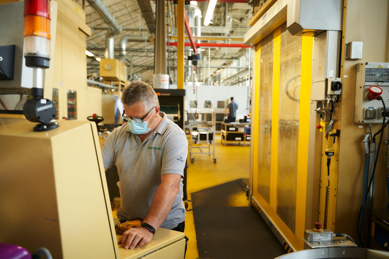 عامل إلى جانب مكبس هيدروليكي يُستخدم لصنع محاور للسيارات الكهربائية
