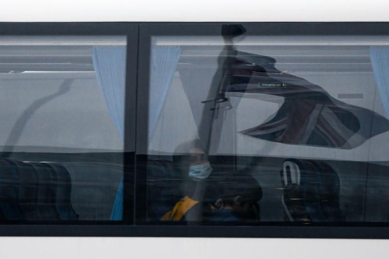 """ينعكس علم الاتحاد البريطاني، المعروف أيضاً باسم """"يونيون جاك""""، في نافذة حافلة عند وصولها مع المسافرين للبقاء في الحجر الصحي في فندق """" راديسون بلو ادوارديان"""" في مطار """"هيثرو"""" في لندن، في المملكة المتحدة، يوم الإثنين 15 فبراير 2021. سيواجه بعض الركاب الذين يسافرون إلى المملكة المتحدة إجراءات حجر صحي أكثر صرامة، بما في ذلك الإقامات القسرية في الفنادق، والاختبارات المتكررة، والتهديد بالغرامات حتى السجن."""