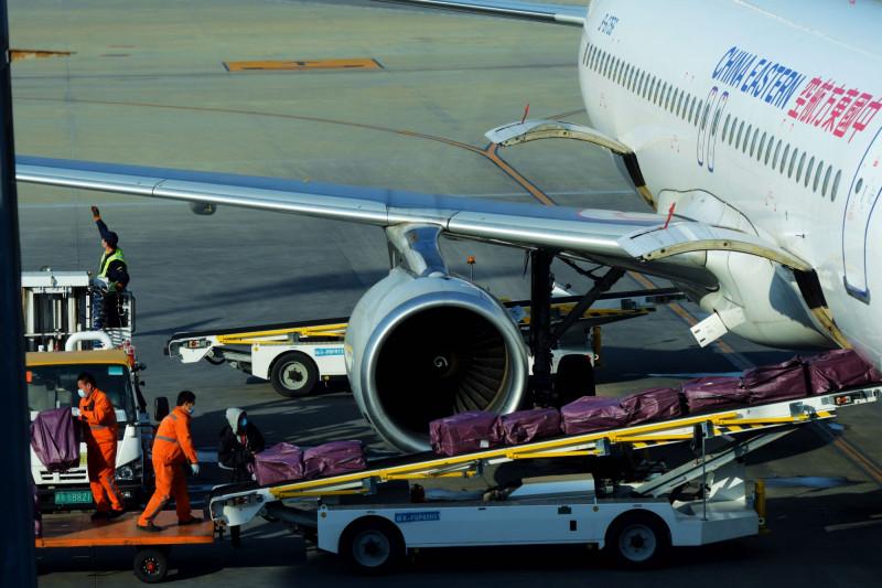 عمال يفرغون طروداً من طائرة تابعة لشركة طيران شرق الصين في تشينغداو، في 21 فبراير