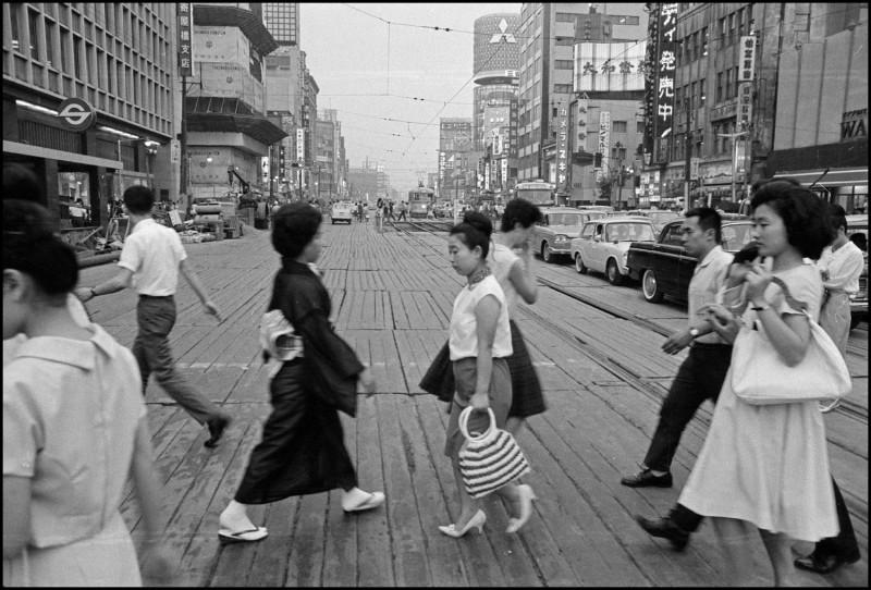 مشاة يعبرون الطريق على ألواح خشبية مؤقتة حيث كانت تتسارع أعمال البناء في طوكيو قبيل الألعاب الأولمبية في عام 1964