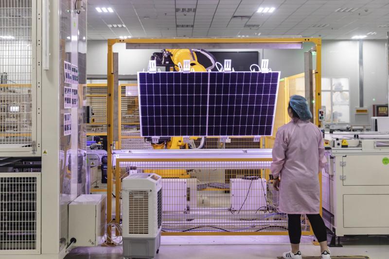 موظف يتفقد ألواح الطاقة الشمسية في مصنع بمدينة شيان في مقاطعة شنشي، الصين في عام 2020