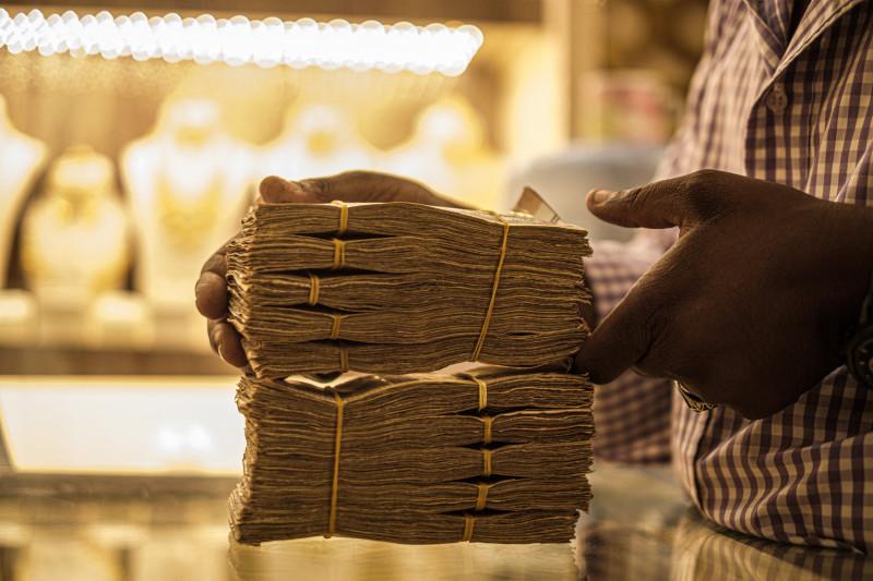 رجل يحمل رزماً من العملة السودانية الجنيه. الخرطوم. السودان