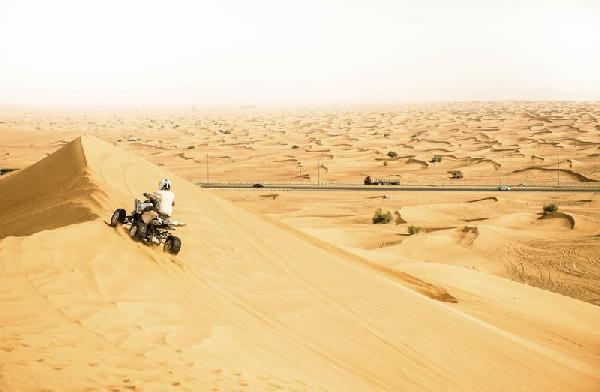 رجل يقود دراجة رباعية بالقرب من الحدود بين الإمارات وعمان