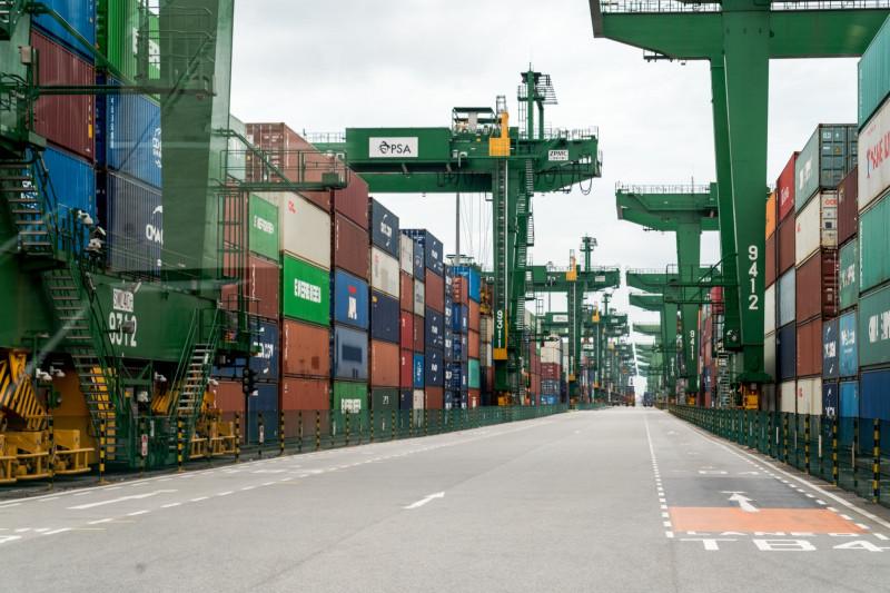 حاويات مكدسة بجوار الرافعات في ميناء سنغافورة