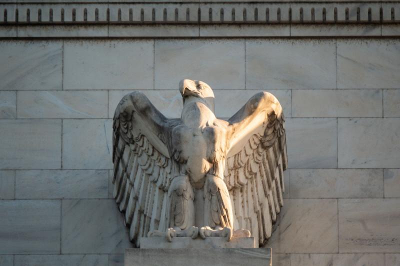 """واجهة مبنى الاحتياطي الفيدرالي في العاصمة الأمريكية واشنطن. ارتفع متوسط عائد السندات دون الدرجة الاستثمارية بنسبة 0.39% منذ بداية العام حتى يوم الخميس الماضي، ولكن يمكن أن تتضرر السندات أكثر إذا ازداد الفزع في الأسواق. ويعود ذلك جزئياً إلى أن أسعار الأوراق المالية حساسة نسبياً تجاه التغير في العائدات حالياً. وإذا كانت موجة البيع منفلتة بشكل كبير، فإن سوق الإصدارات الجديدة قد تغلق فعلياً كما حدث في 2013 عندما قفزت العائدات بعد أن تحدث الفيدرالي عن تقليص برنامج التيسير الكمي وهي فترة تعرف بـ""""نوبة الغضب""""."""
