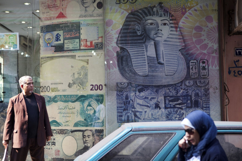 رجل يقف أمام محل للصرافة في وسط العاصمة المصرية القاهرة> يتوقع محللو شركة بلتون المالية ارتفاع قيمة الجنيه نظراً للقدرة على تغطية 80% من الفجوة التمويلية بالنقد الأجنبي في مصر، وذلك رغم تأثر السياحة بشكل كبير.