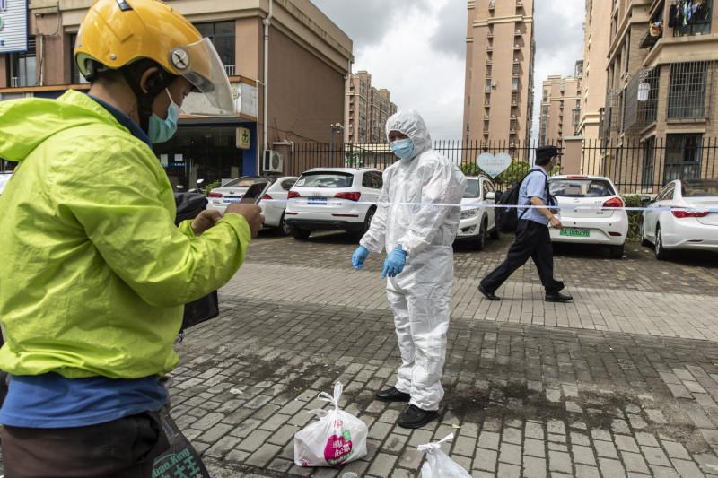 موظف يقوم بتوصيل الطعام والمؤن الضرورية للسكان في الأحياء الخاضعة للحجر الصحي في شنغهاي الصين