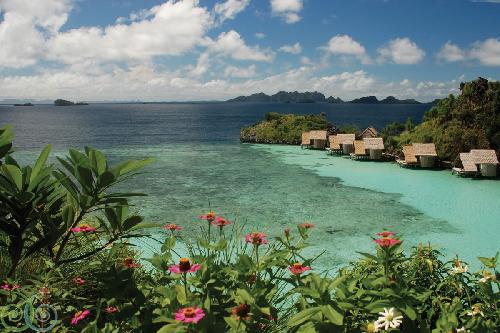 """أكواخ خشبية تطفو فوق الماء في مجموعة جزر راجا أمبات في """"ميسول""""."""