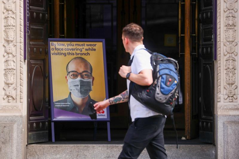 """لافتة تطلب من العملاء ارتداء الأقنعة الطبية. وذلك عند مدخل فرع بنك """"ناتويست"""" في مدينة لندن، المملكة المتحدة، في يونيو 2021. وقد تركت ثلاث عمليات إغلاق آثارا عديدة على المركز المالي للمملكة المتحدة"""