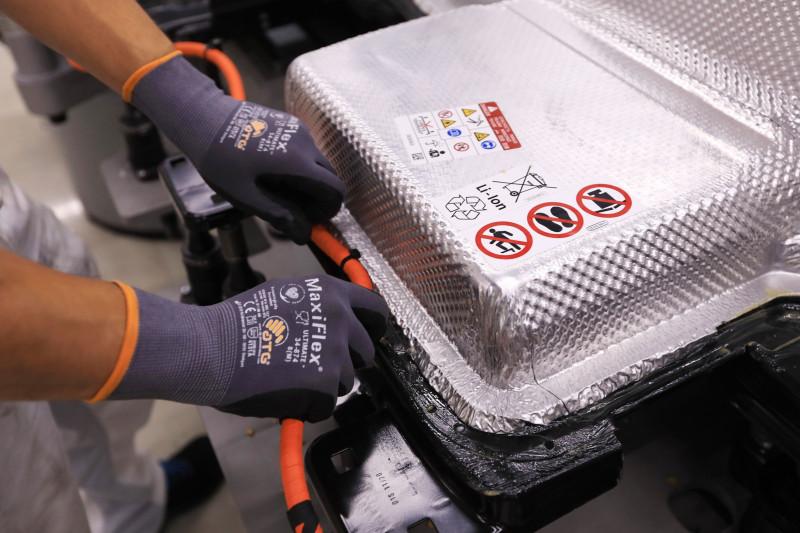"""موظف يؤمن كابل حزمة البطارية في سيارة كهربائية فولكس واجن. قد تجد الشركة نفسها أمام تحديات في حال منعت """"اس كيه اننوفيشن"""" من تزويدها بالمكونات اللازمة لصناعة مصفوفة محرك كهربائي"""