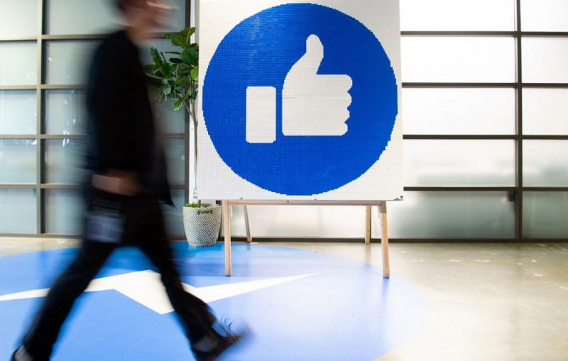 رجل يعبر من أمام لوحة لإشارة الإعجاب لموقع التواصل الاجتماعي فيسبوك