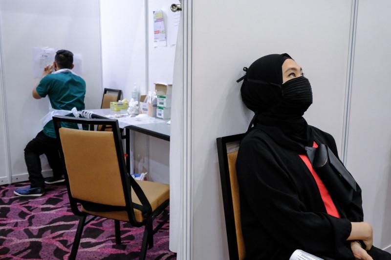 """امرأة تنتظر تلقّي جرعة من لقاح """"كوفيد-19"""" من شركة """"أسترازينيكا""""، في مركز تطعيم خاص تم إنشاؤه في سلانغور، ماليزيا."""