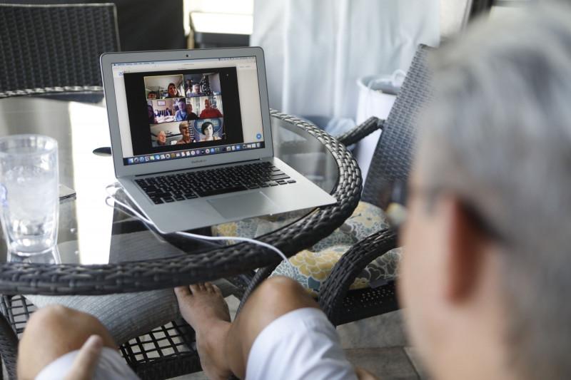 رجل يجري محادثة مصورة من المنزل عبر تطبيق زووم.  قد يكون التباعد الاجتماعي الذي فرضه كوفيد-19 على المجتمع علمنا كيفية استخدام الخدمات عبر الإنترنت بطريقة أكثر إنتاجية