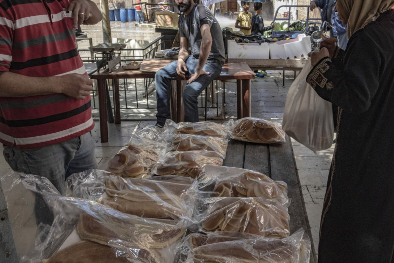 سيدة تشتري الخبز من أحد البسطات الشعبية في مدينة صيدا