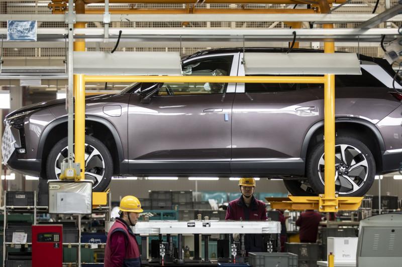 """عمال يعملون على تركيب بطاريات لسيارة رياضية كهربائية فى منشأة إنتاج لشركة """"نيو"""" في مدينة خفى بالصين"""