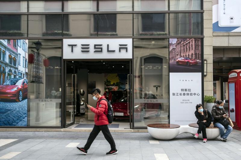 """متسوق يمر بالقرب من صالة عرض """"تسلا"""" في شنغهاي خلال شهر مارس الماضي"""