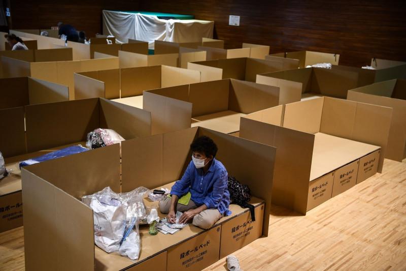 أسرة من الورق المقوى في مأوى للسكان المتضررين من الفيضانات