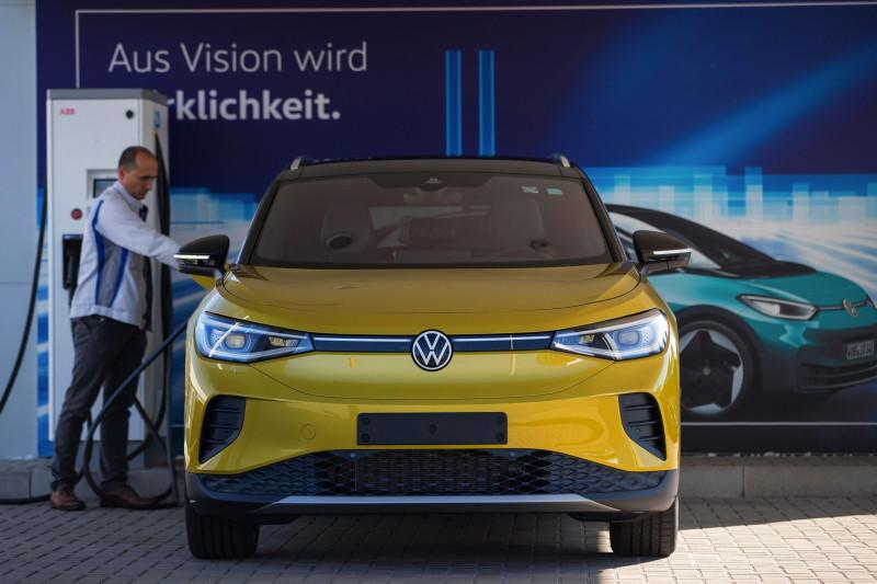 موظف يقوم بتوصيل قابس شحن كهربائي بسيارة فولكس واجن الرياضية الكهربائية (ID.4) في مصنع الشركة في تسفيكاو. ألمانيا