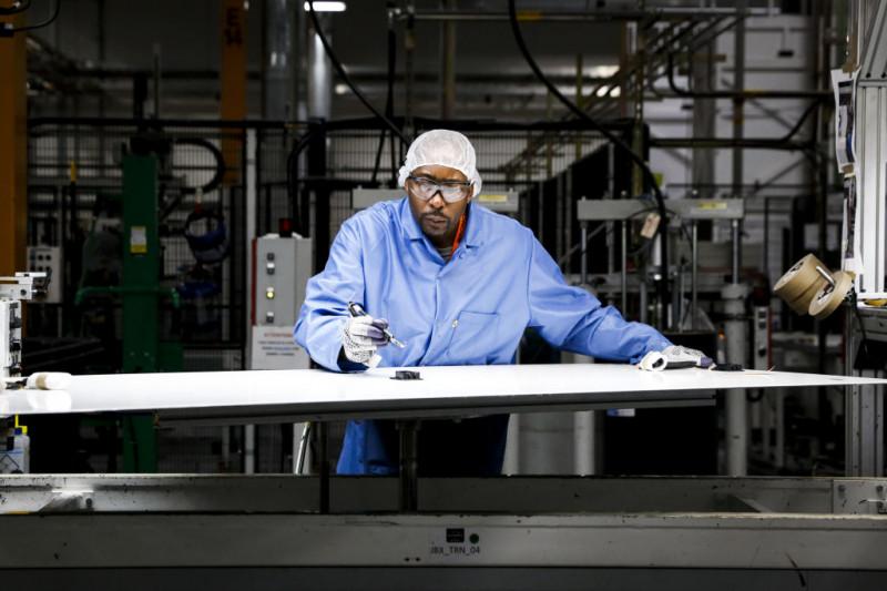 عامل في مصنع للطاقة الشمسية بولاية أوريغون في الولايات المتحدة