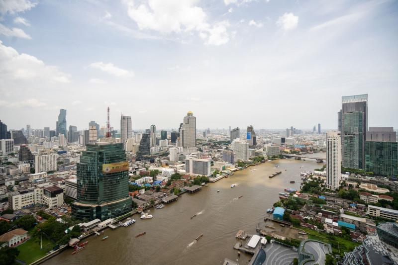 """نهر تشاو فرايا والمباني المحيطة كما تبدو من مبنى شاركت بتطويره """"تشاريون بوكفاند"""". سليل الأسرة مالكة الشركة العريقة يعتزم اقتناص فرص من تعثر شركات تايلندية إبان الوباء"""