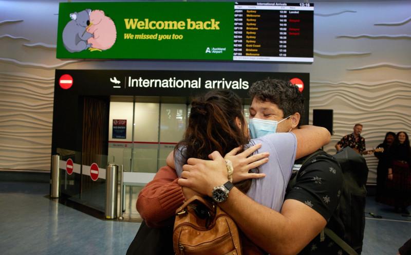 """أشخاص يتعانقون أثناء لم شملهم في صالة القادمين بمطار أوكلاند الدولي، في نيوزيلندا. تتحد بعض الأماكن بما في ذلك، أستراليا ونيوزيلندا، وسنغافورة، وهونغ كونغ معاً لخلق """"فقاعات السفر"""" والتي تسمح للمواطنين بالزيارة دون المكوث في الحجر الصحي الإلزامي."""