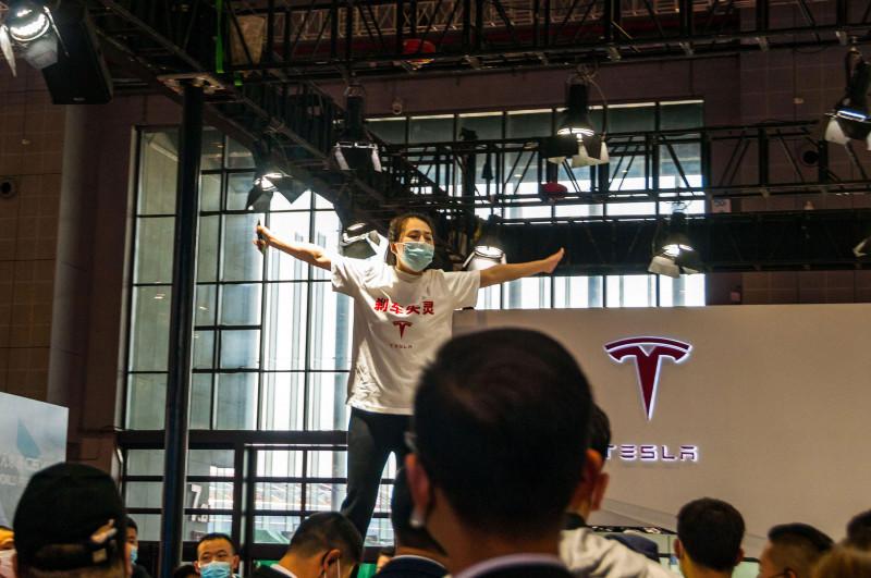 """امرأة تقف فوق سطح سيارة """"تسلا"""" احتجاجاً خلال معرض شنغهاي للسيارات 2021"""