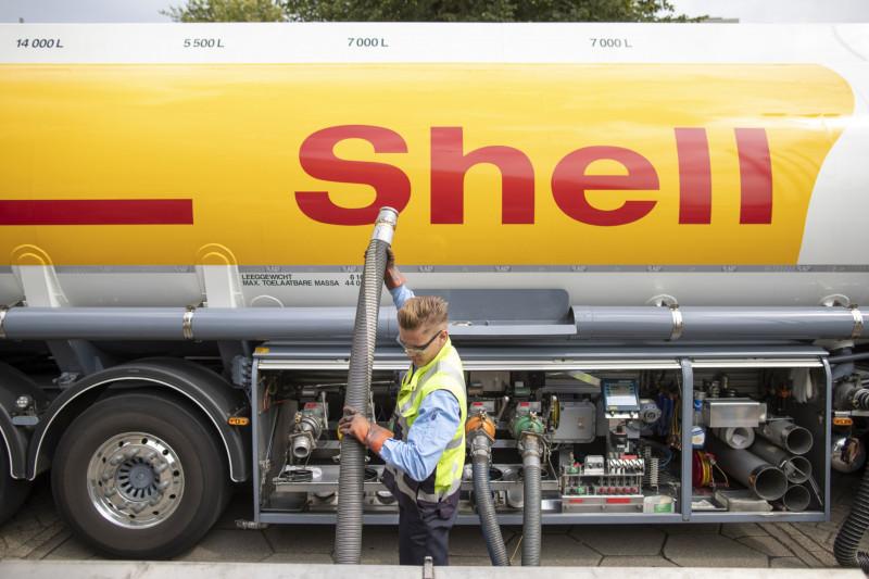 """عامل يستخدم خرطوماً لضخ الوقود من شاحنة صهريجية تابعة لشركة """"شل"""" في محطة وقود"""