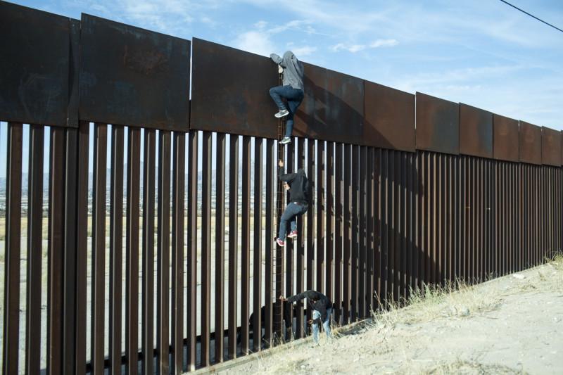مهاجران يحاولان تسلّق الجدار بين الحدود المكسيكية والأمريكية