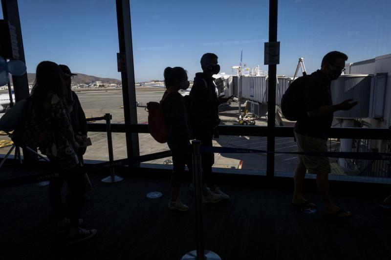 """مسافرون يرتدون أقنعة واقية على متن رحلة تابعة لشركة """"يونايتد إيرلاينز"""" في مطار سان فرانسيسكو الدولي"""