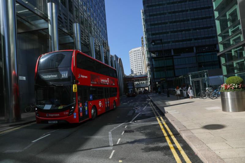 """حافلة تعبر """"كناري وارف"""" الحي المالي في العاصمة البريطانية لندن ويظهر في الصورة المقر الرئيسي لمصرف كريديت سويس"""