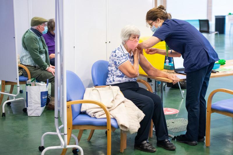 زائر يتلقى لقاح Covid-19 في مركز تطعيم شامل في مضمار Epsom Downs لسباق الخيل في المملكة المتحدة في يناير  2021