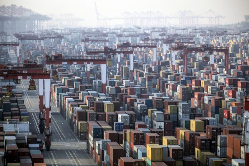 """حاويات شحن بجانب رافعات جسرية في ميناء يانغ شان ديبووتر في شنغهاي في الصين يوم الاثنين 11 يناير 2021. وكان الرئيس دونالد ترامب نشر تغريدته الشهيرة """"الحروب التجارية جيدة وسهلة الفوز"""" في 2018 عندما بدأ فرض تعريفات على حوالي 360 مليار دولار من الواردات من الصين، وتبين أنه كان مخطئا في حساباته."""