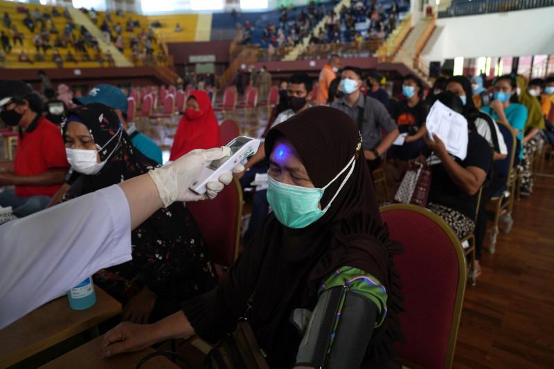 قياس حرارة مواطنة في أحد مراكز التلقيح في جاكرتا إندونيسيا