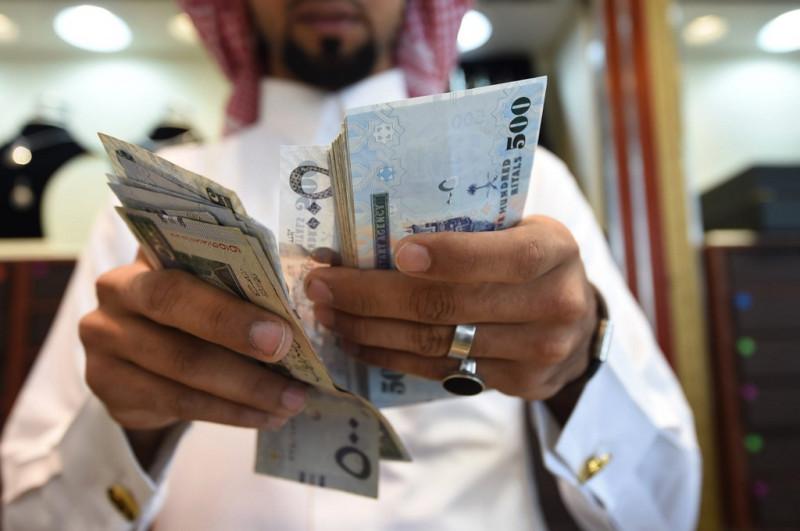 مواطن سعودي يعد أوراق نقد من فئة 500 ريال. خلال الشهور التسعة الأولى من العام الحالي، وبلغت إصدارات الدين السعودية حوالـي 207 مليـــارات ريـــال، شـكلت الإصـدارات المحليـة منهـا 78.3%.