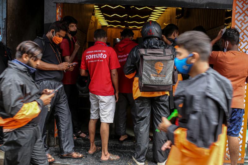 """ينتظر عمال التوصيل لشركات """"زوماتو"""" و""""سنتر"""" و""""سويغي"""" التي تديرها """"بوندل تكنولوجيز""""، تسلُّم الطلبات خارج مطعم في مومباي بالهند، يوم الجمعة 16 يوليو 2021. جرى الاشتراك في الاكتتاب العام الأولي لـ""""زوماتو"""" بقيمة 1.3 مليار دولار بالكامل في اليوم الأول من البيع، بعد أن قدمت الصناديق الرئيسية، بما في ذلك شركة """"بلاك روك""""، عروضاً لشراء 35 ضعفاً من الأسهم التي عُرضت عليها"""