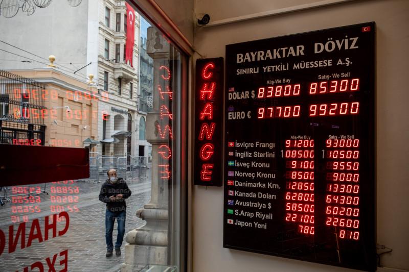 مواطن يمرّ أمام لوحة عليها سعر الليرة التركية مقابل العملات الأساسية في اسطنبول