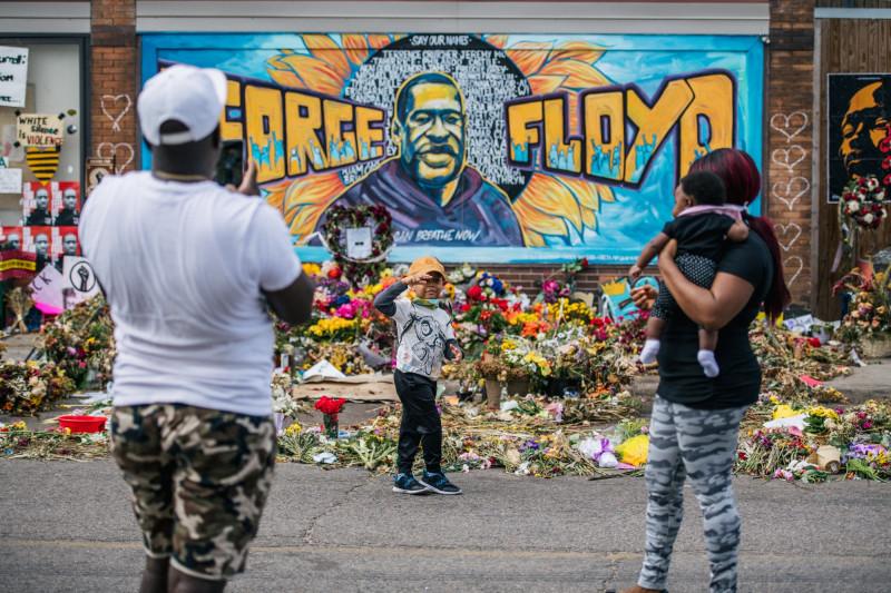 عائلة تأخذ صورة أمام جدارية جورج فلويد في مينابولس، 10 يونيو