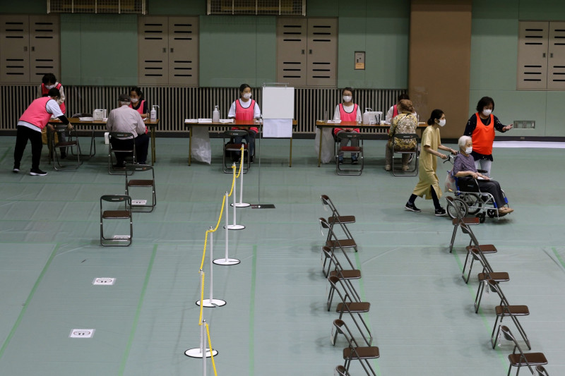 """امرأة تصل على كرسي متحرك لتلقي لقاح """"فايزر-بايونتيك"""" في مركز رياضي في أوساكا باليابان أول يونيو"""
