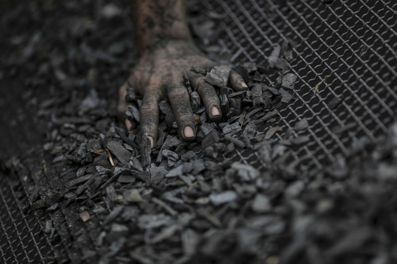 عامل يستخدم مصفاة لتنقية الفحم في مومباي، الهند