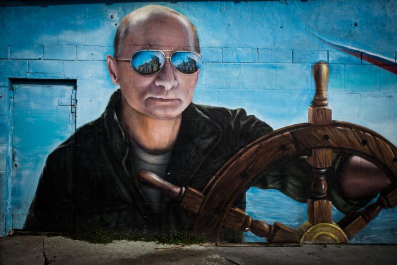 لوحة جدارية تظهر الرئيس الروسي فلاديمير بوتين يقود مركباً، على جانب أحد المباني في يالطا، شبه جزيرة القرم