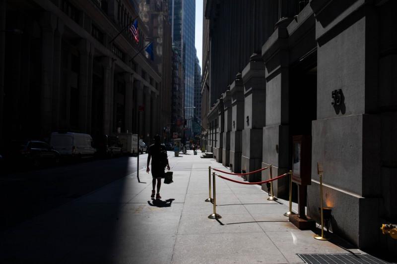 أحد المشاة يسير في شارع وول ستريت قرب بورصة نيويورك