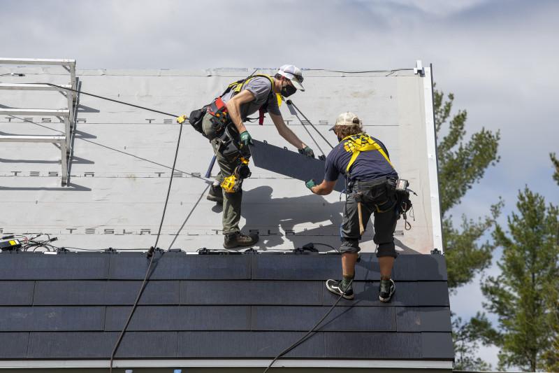 """عمال يقومون بتركيب الألواح الشمسية من شركة """"تسلا"""" على سقف أحد المنازل في وارن، فيرمونت بالولايات المتحدة"""